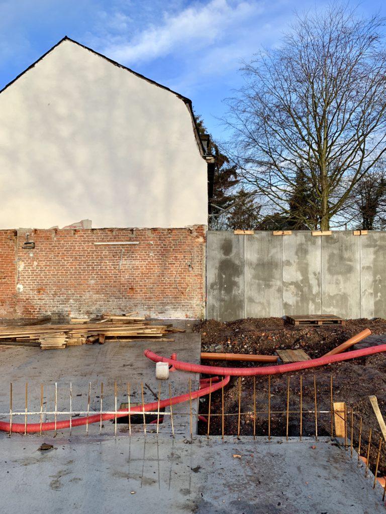 Le radier en béton est coulé et les L de soutènement sont posés sur la limite de propriété séparant le projet de la maison des voisins